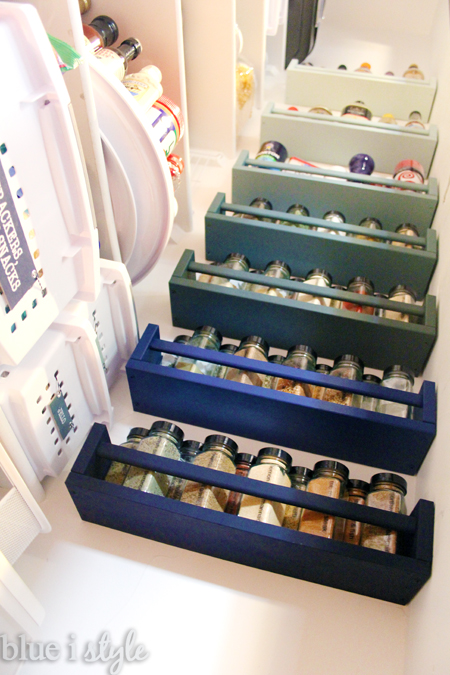 Ombre colored spice racks on wall of pantry