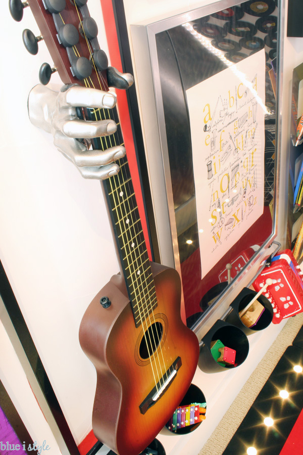 This silver hand guitar holder makes a big statement on this music gallery wall.