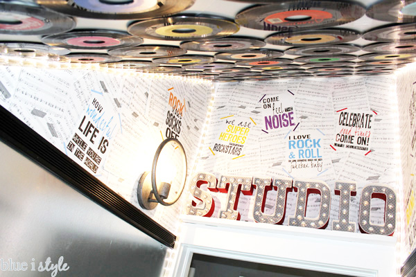 "DIY sheet music wallpaper, music lyrics posters, and a ceiling covered in vinyl records make for a very cool ""studio"" playroom under the stairs."