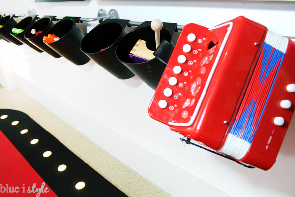 IKEA Bygel storage rails for organizing and storing kids musical toys, including a red toy accordian.