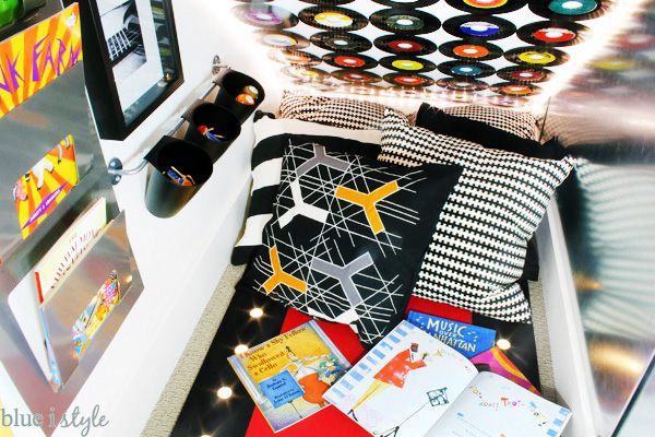 Under stairs reading nook with a collection of music books for kids in a music themed playroom.