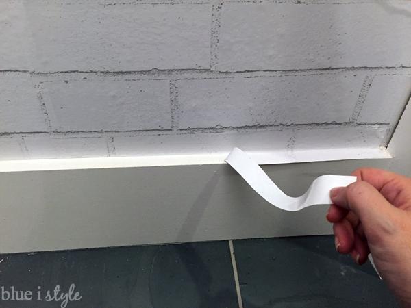 Trimming temporary wallpaper at baseboard