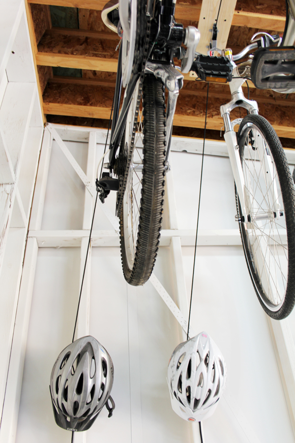 A bike pulley system keeps bikes out of the way in the garage. Store bike helmets