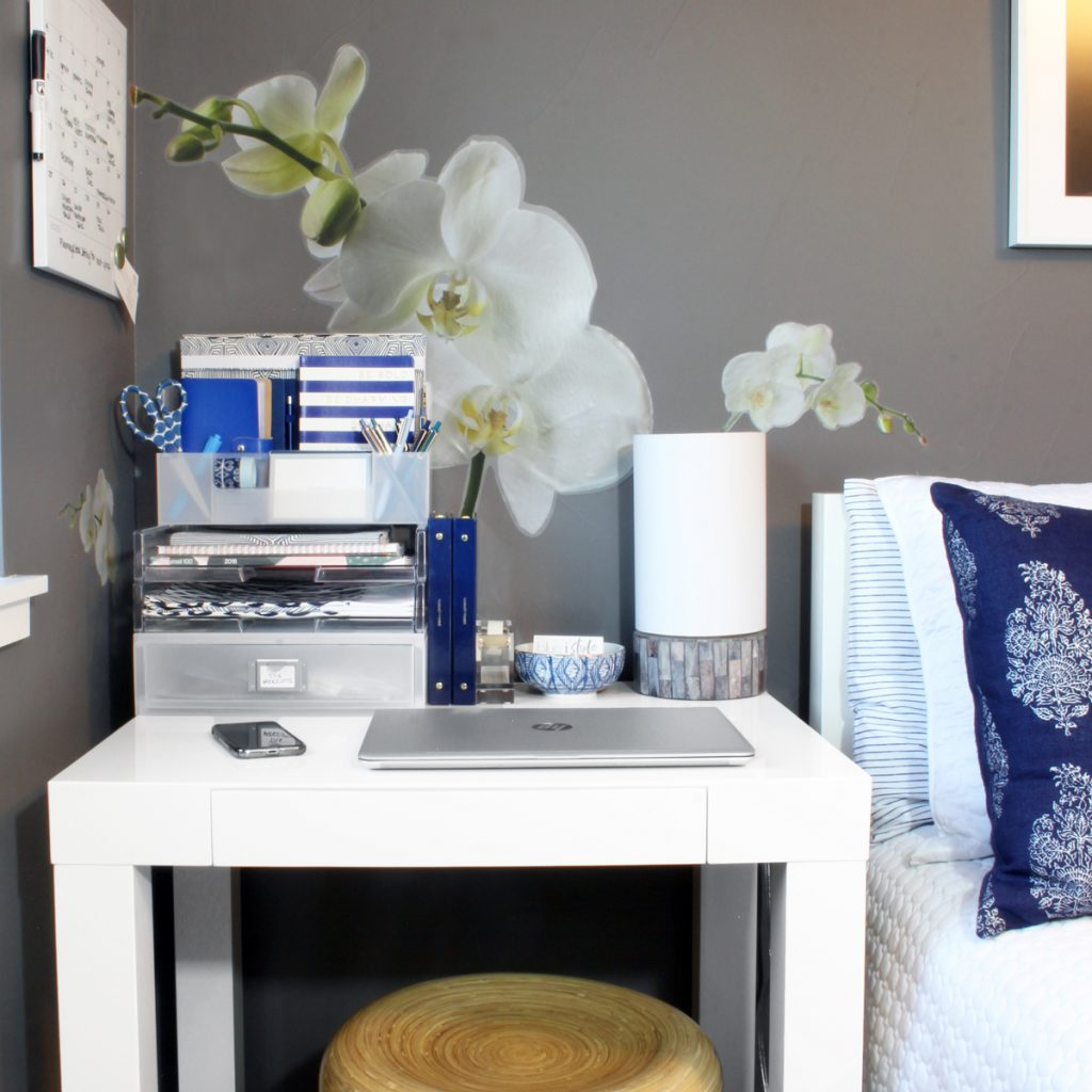 White writing desk in place of nightstand in guest room with dark gray walls