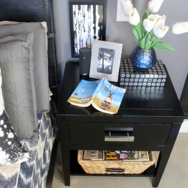Black nightstand with silver handle blue vase and magazine basket