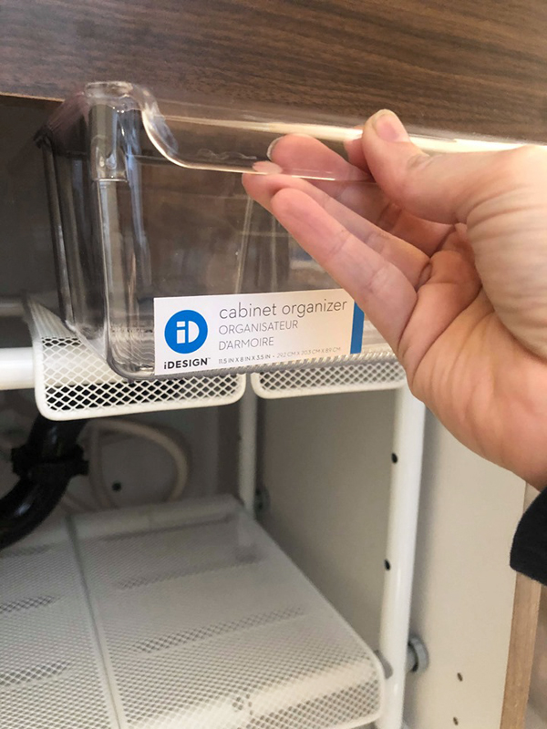 Clear container with a handle to organize under the bathroom sink