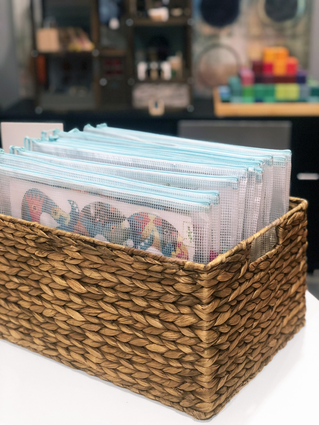 store puzzles in zippered pouches in a wicker basket