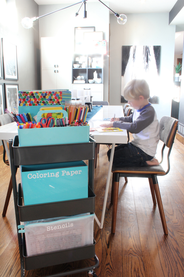 Little boy drawing at kitchen table with rolling art cart next to him