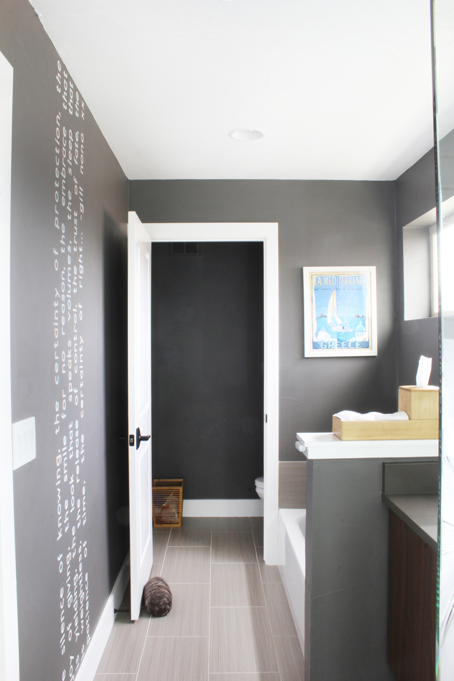white vertical wall quote floor to ceiling on dark gray bathroom wall