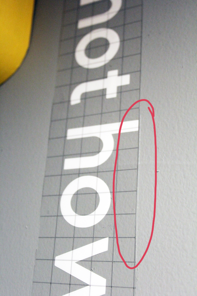 Lining up Cricut transfer tape guidelines with level line to apply wall words