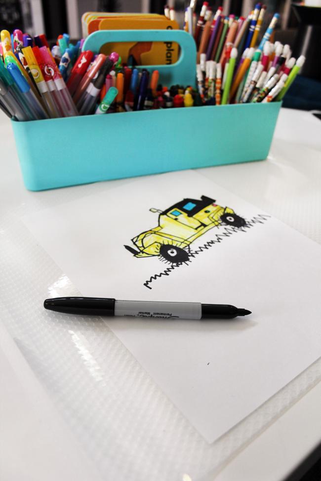 Clear shelf liner under kids art with sharpie marker