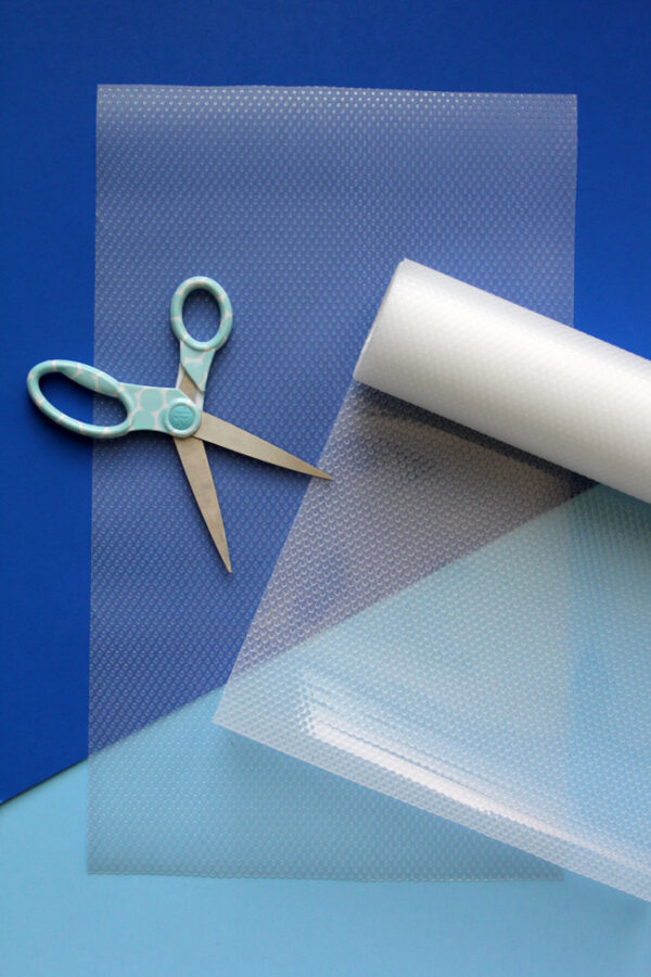 clear shelf liner and scissors on blue background