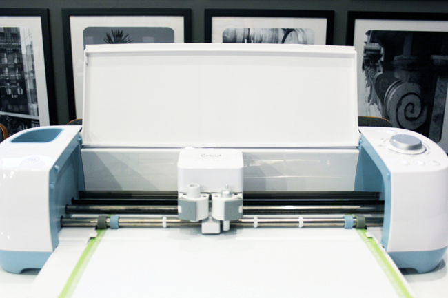 Cricut Explore Air machine cutting white vinyl on green mat