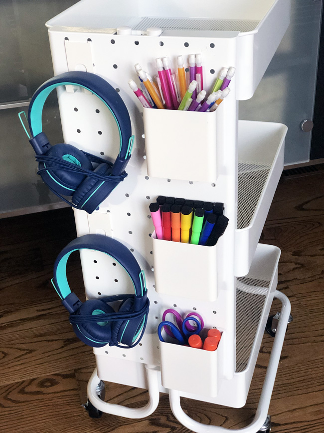 Pegboard on a rolling cart with hooks for headphones and cups filled with pencils and markers