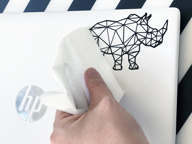 Adding a vinyl rhino sticker to a laptop