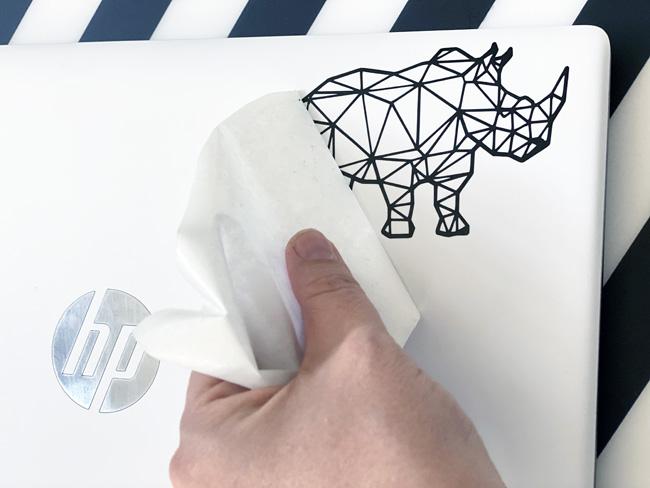 Adding a vinyl rhino sticker to a laptop