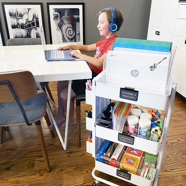 Rolling cart with distance learning school supplies by the kitchen table