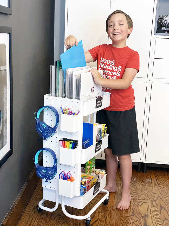 Boy getting school supplies from rolling homeschool cart in kitchen