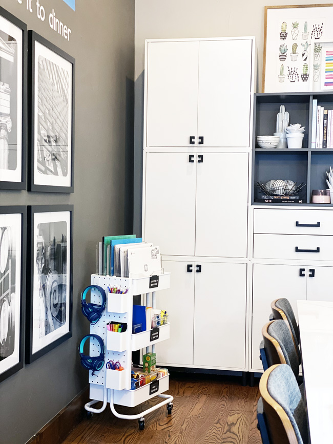 Rolling school cart in corner of kitchen with white cabinets