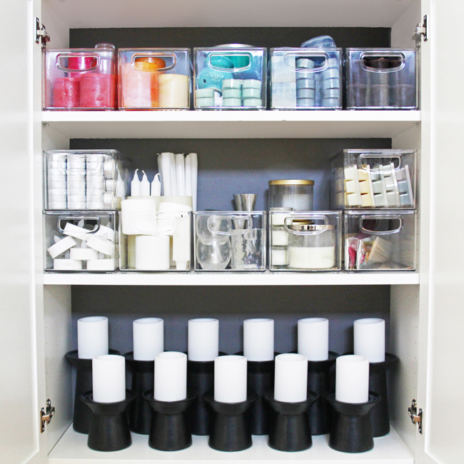 an organized candle storage cabinet with candles in rainbow order